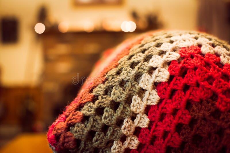 红色被定调子的钩针编织毯子在一个沙发背面在家庭娱乐室 图库摄影