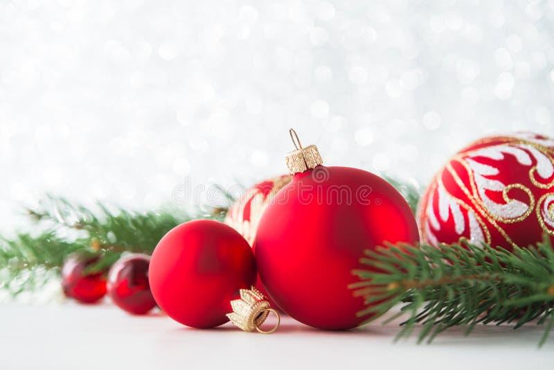 红色装饰品和xmas树在闪烁假日背景 圣诞快乐看板卡 库存图片