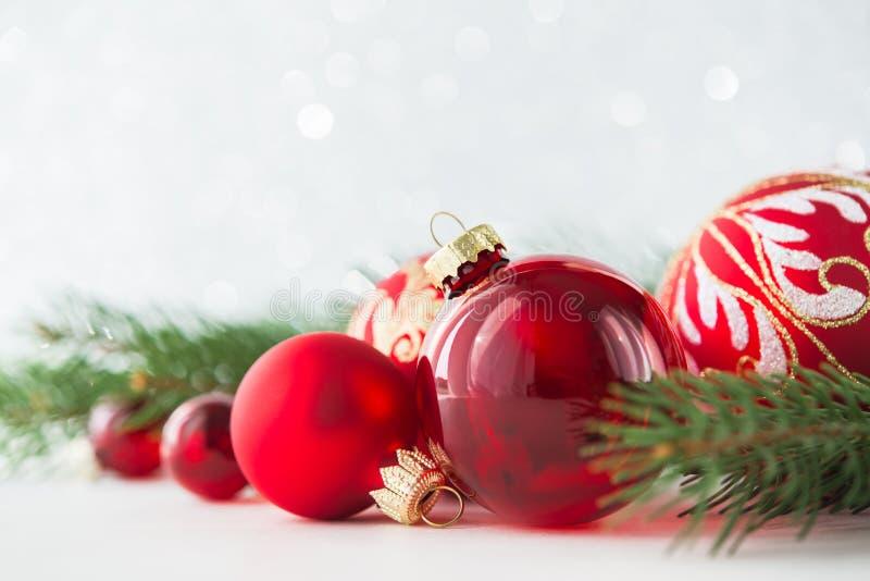红色装饰品和xmas树在闪烁假日背景 圣诞快乐看板卡 免版税库存图片