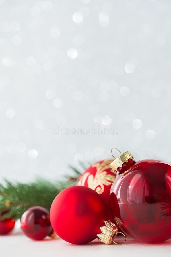 红色装饰品和xmas树在闪烁假日背景 圣诞快乐看板卡 库存照片