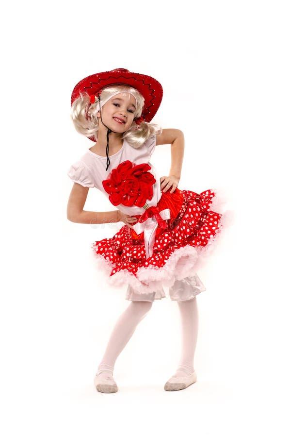 戴红色裙子、T恤杉有花的和牛仔帽的逗人喜爱的矮小的白种人女孩隔绝在白色背景 她跳舞 免版税库存图片