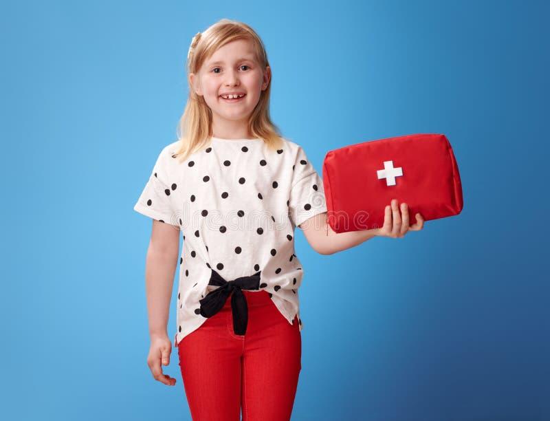 红色裤子的微笑的现代女孩在显示急救包的蓝色 图库摄影