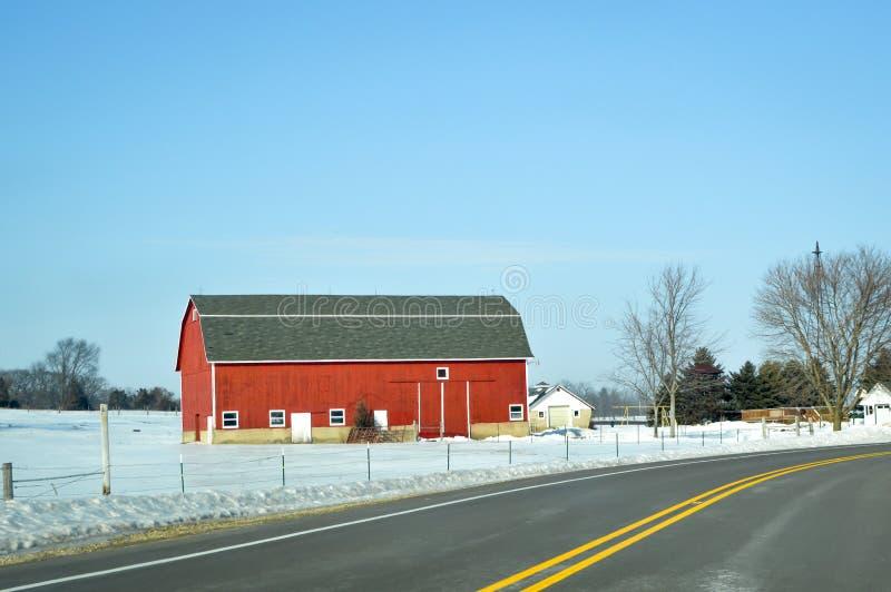 红色谷仓,冬天,乡下公路 免版税库存图片