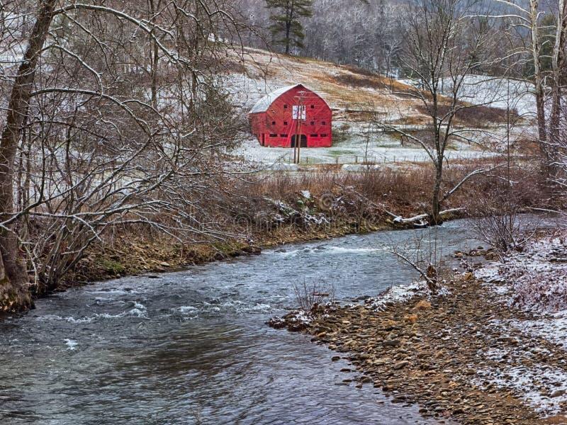 红色谷仓在山河附近的冬天 图库摄影