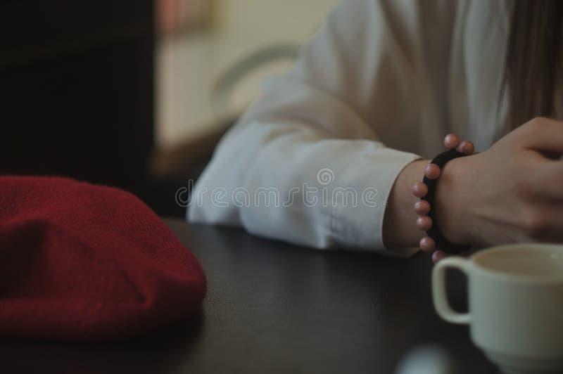 红色贝雷帽、手和杯子 免版税库存照片