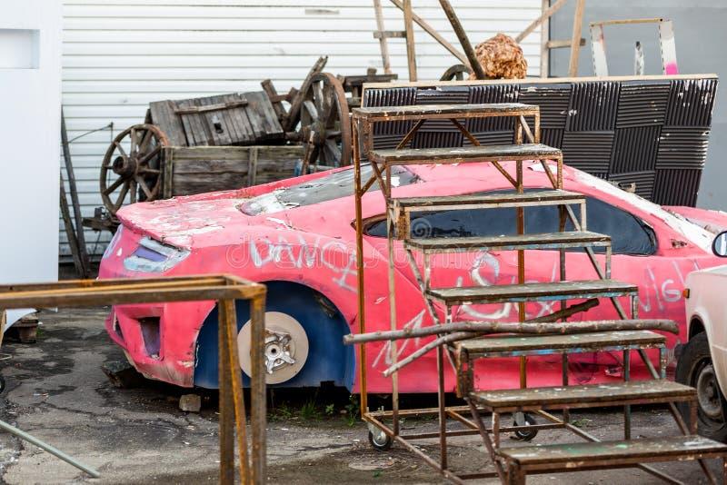红色跑车老破旧的模型  生锈的金属结构,电影风景的老打破的装饰在后院的 免版税库存照片