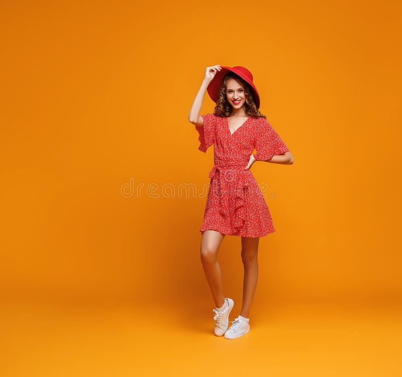 红色跳跃在黄色背景的夏天礼服和帽子的概念愉快的情感年轻女人 免版税库存照片