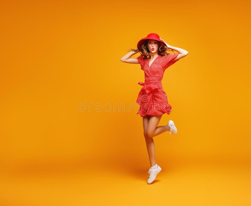 红色跳跃在黄色背景的夏天礼服和帽子的概念愉快的情感年轻女人 免版税库存图片