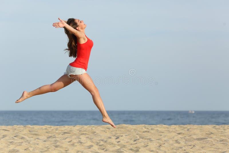 红色跳跃的青少年的女孩愉快在海滩 库存图片