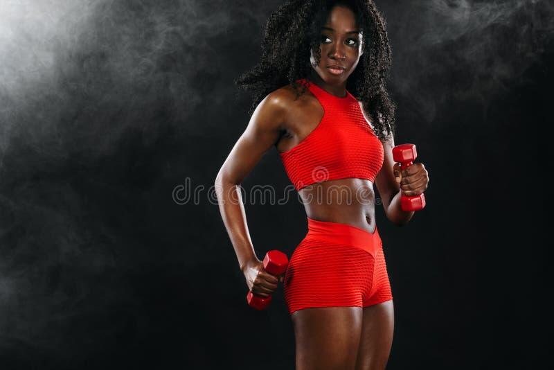 红色运动服的运动的适合的黑人皮肤妇女,有哑铃的行使的运动员在黑暗的背景做健身 免版税库存图片
