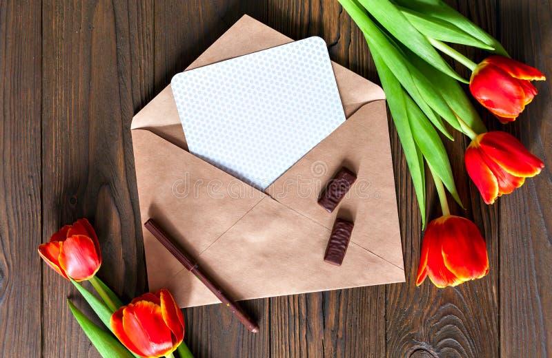 红色郁金香和卡拉服特信封在木背景 库存图片