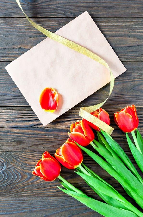 红色郁金香和卡拉服特信封在木背景 免版税库存图片