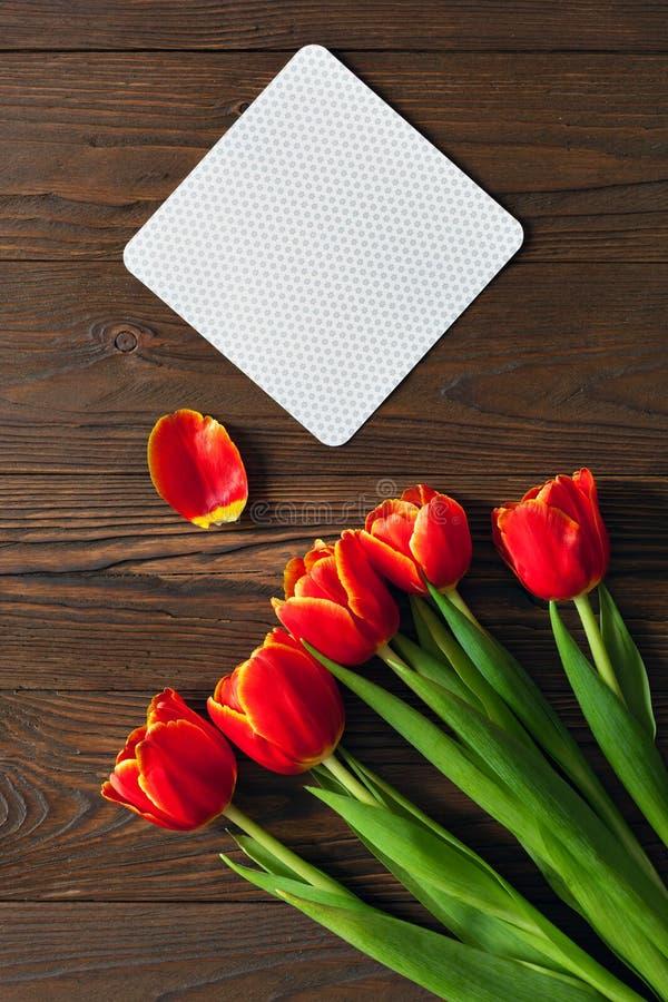 红色郁金香和卡拉服特信封在木背景 免版税图库摄影