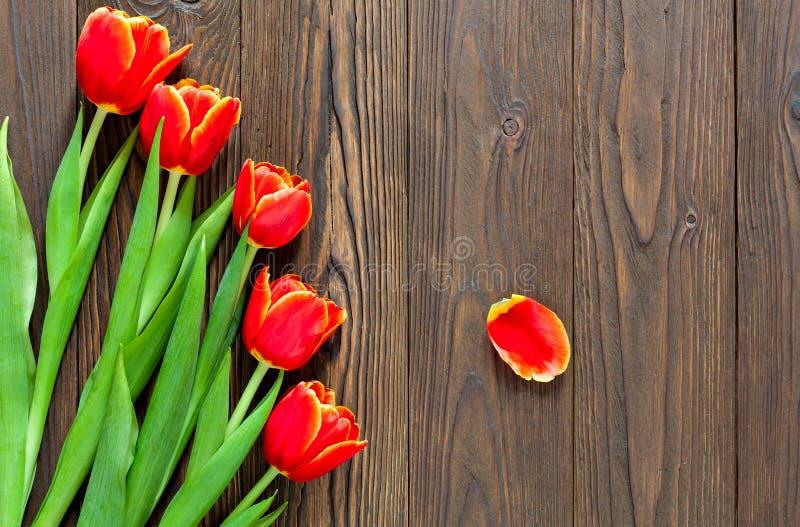红色郁金香和卡拉服特信封在木背景 免版税库存照片