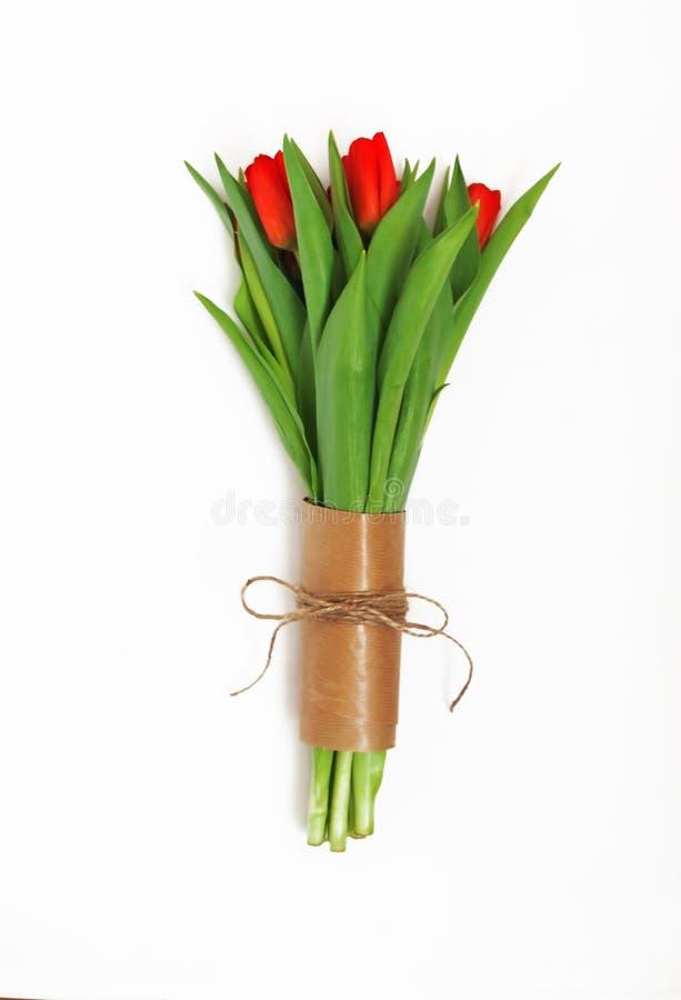 红色郁金香花束在减速火箭的样式isola的牛皮纸包装了 库存图片