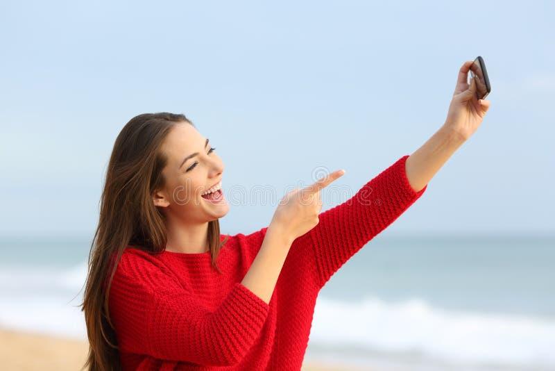 红色采取的selfies的愉快的女孩在海滩 免版税库存照片