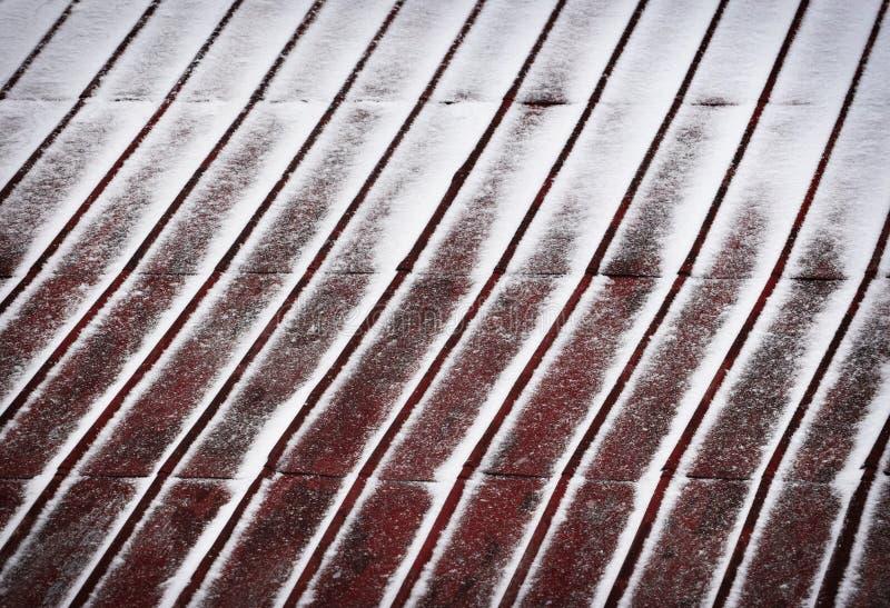 红色金属屋顶拂去灰尘与雪 免版税库存照片