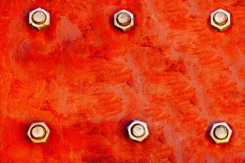 红色金属片绘与强的红色和橙色颜色和固定与六大钢闩拧紧当纹理背景 免版税库存图片