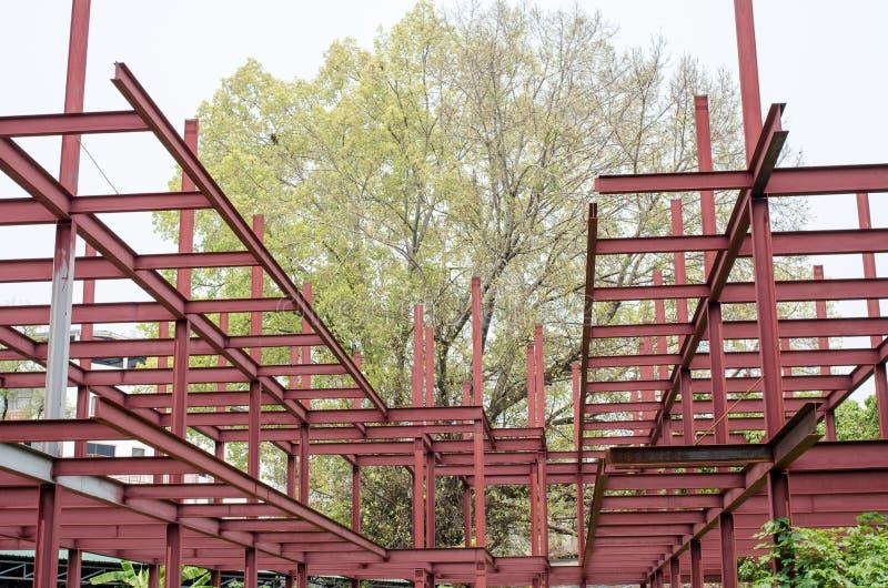 红色钢&big绿色树 免版税库存照片