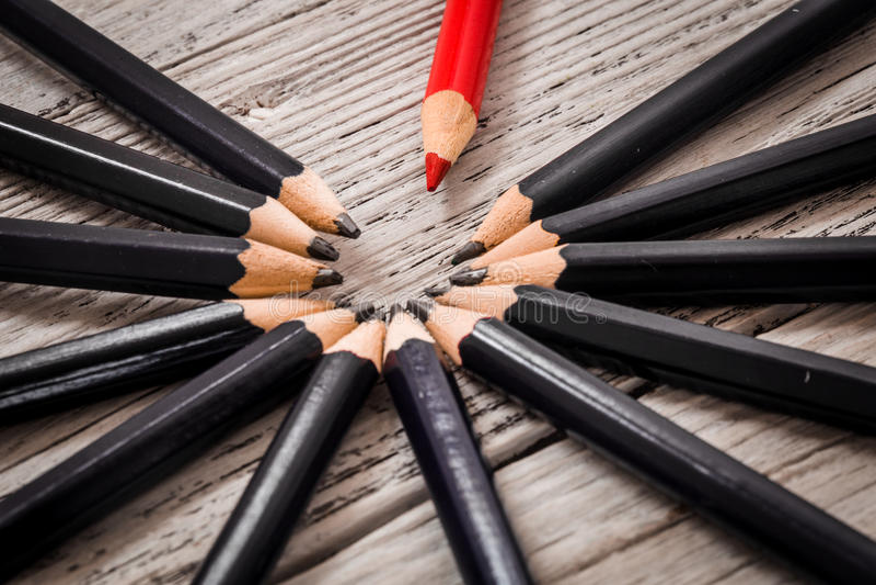 红色铅笔从黑色人群在木白色背景的引人注意 库存图片