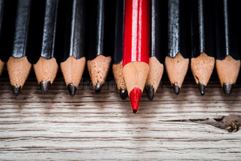 红色铅笔从黑色人群在木白色背景的引人注意 库存照片