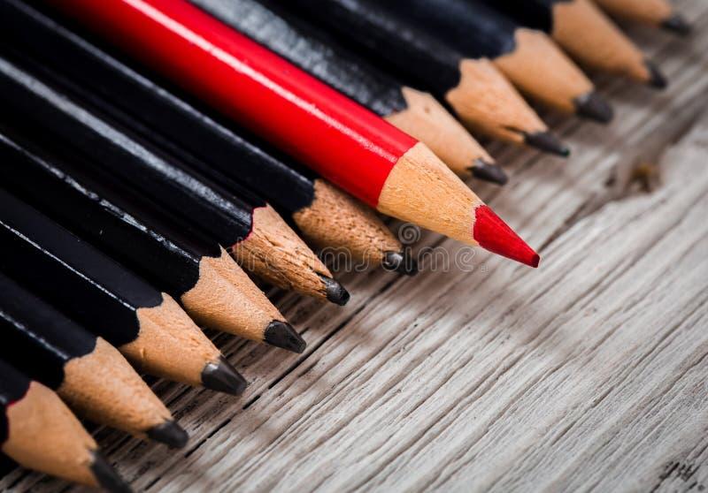 红色铅笔从黑色人群在木白色背景的引人注意 免版税库存照片