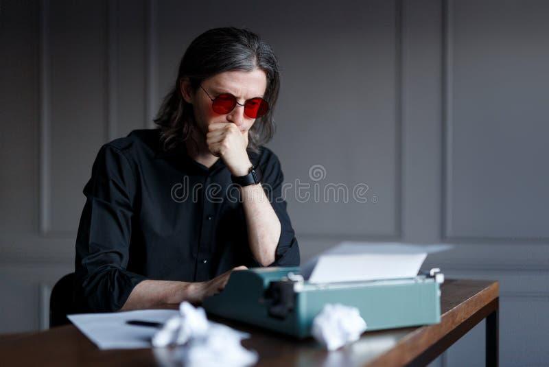 红色镜片和黑衬衣的年轻作家,考虑新书,运作在打字机,供以座位在桌上 库存图片