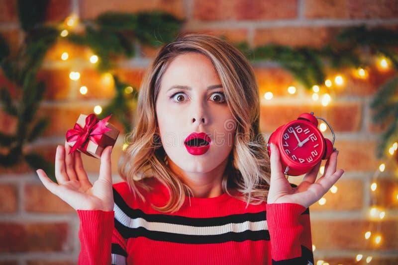 红色镶边毛线衣的女孩有礼物盒和闹钟的 库存图片