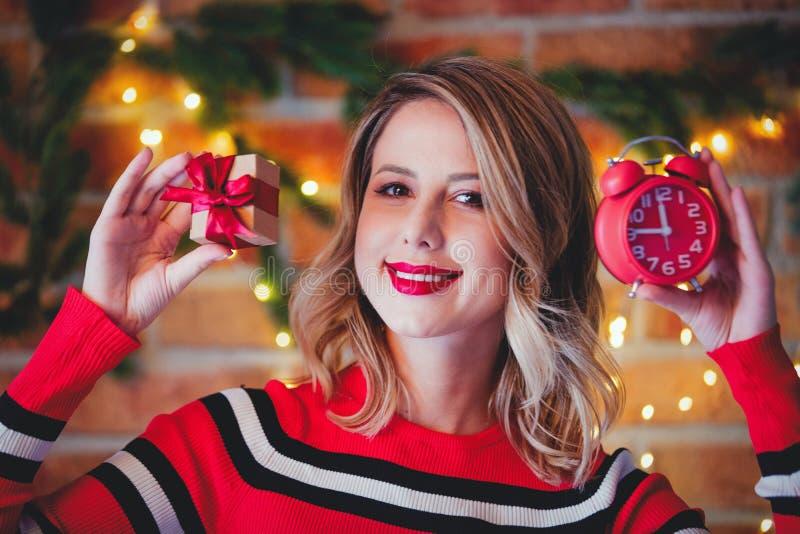 红色镶边毛线衣的女孩有礼物盒和闹钟的 库存照片