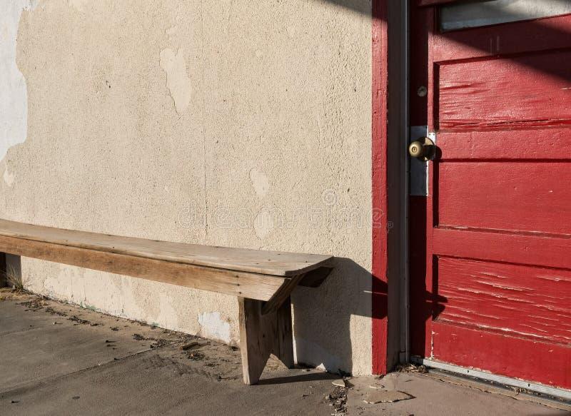 红色门和长凳 免版税库存图片