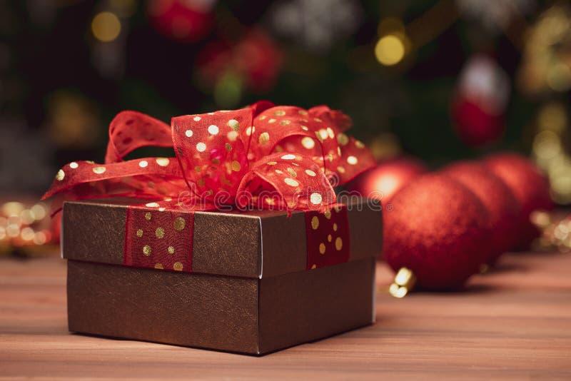 红色闪烁球的关闭,在焦点外面的一个礼物盒在前面 免版税图库摄影
