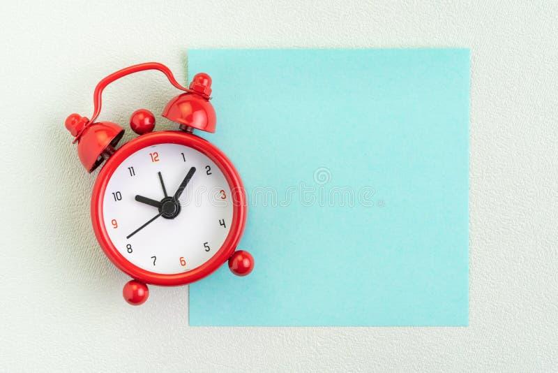 红色闹钟平的位置有空白的稠粘的笔记的在白色背景的消息的与拷贝空间使用作为时间,最后期限,停止 免版税库存图片