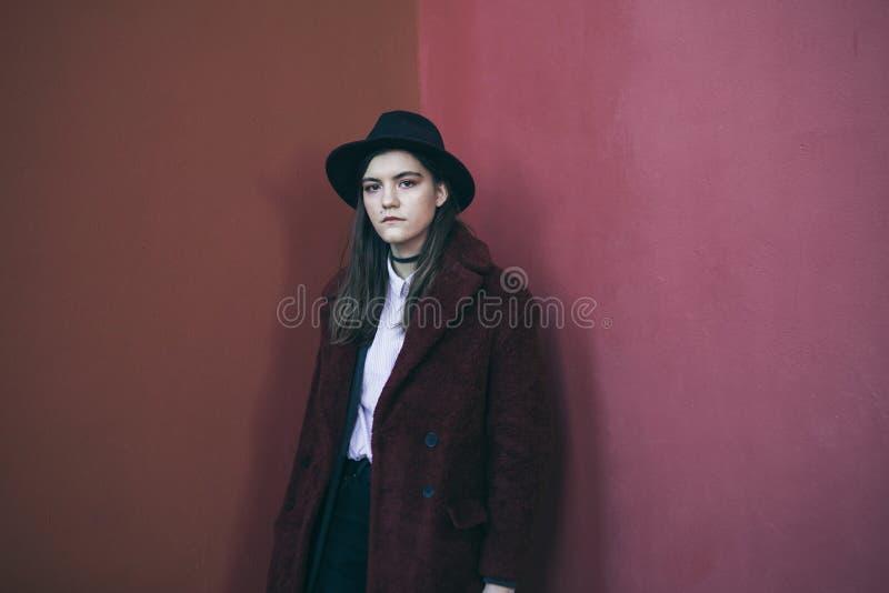 红色青少年的女孩画象 时髦的帽子和毛皮大衣 严肃的表情 忧郁的心情 忽略和 库存照片