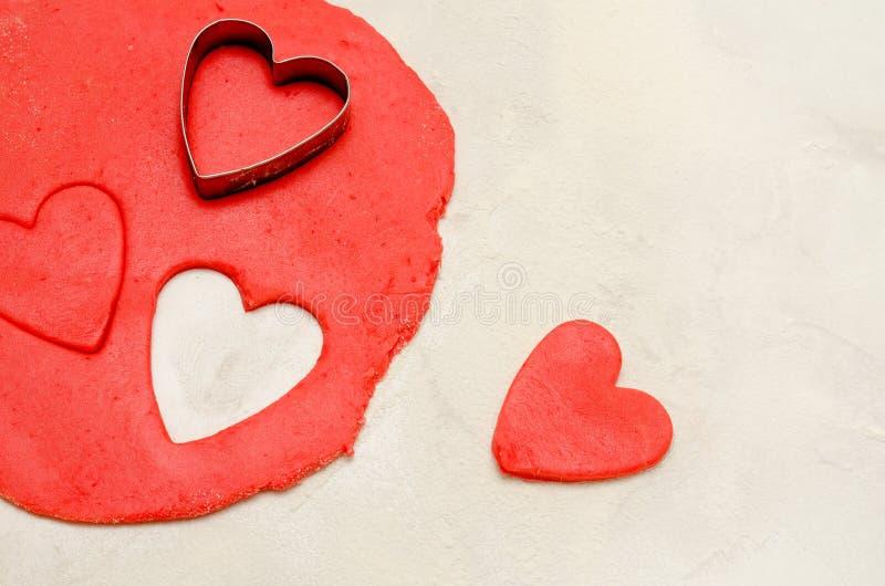 红色面团以削减和删去在一张白色桌,文本的空间上的心脏的形状 免版税库存图片