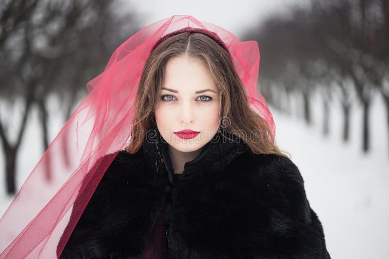 红色面纱的女孩在雪在冬天 库存图片