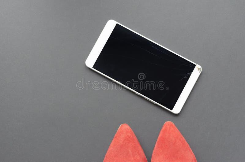 红色鞋子和残破的电话在灰色背景 库存图片