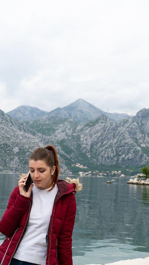 红色顶头少女谈话由有红色夹克的手机在湖 与灰色山的科托尔海湾在湖 免版税库存图片
