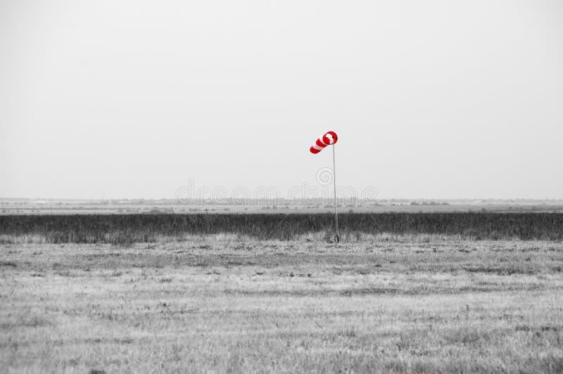 红色风向袋在成为不饱和的大草原 免版税图库摄影