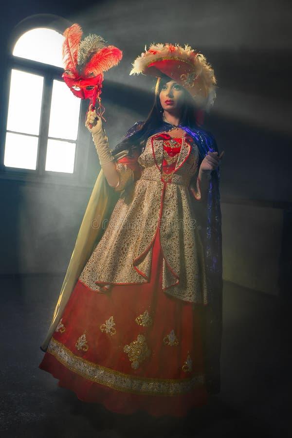 红色中世纪服装的妇女有面具的 免版税库存照片