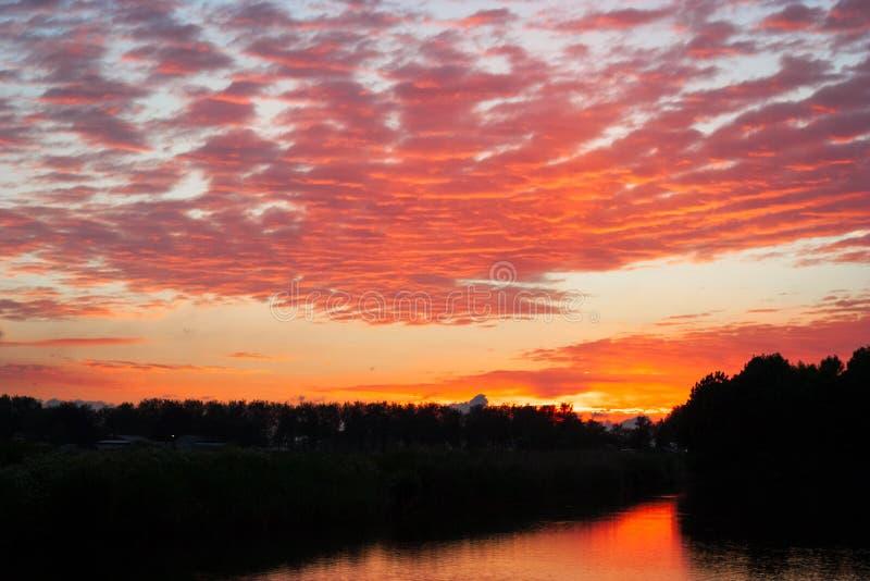 红色高积云五颜六色的云彩scape在日落的在荷兰扁圆形干酪,荷兰附近 免版税库存照片