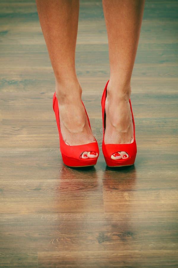 红色高跟鞋钉牢在女性腿的鞋子 免版税库存图片