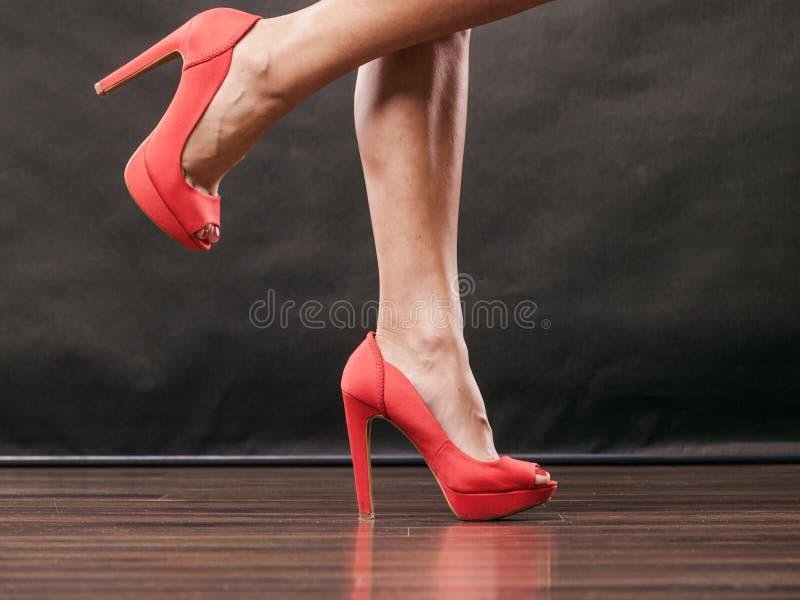 红色高跟鞋钉牢在性感的女性腿的鞋子 库存照片