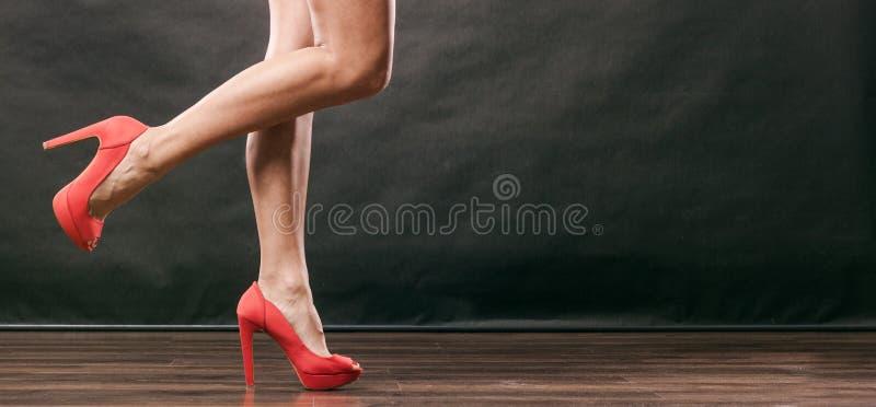 红色高跟鞋钉牢在性感的女性腿的鞋子 免版税库存图片