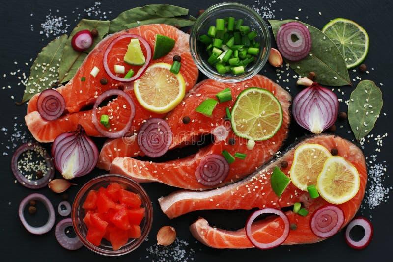 红色鱼三文鱼Faw内圆角用在黑暗的背景,顶视图的香料 免版税库存照片