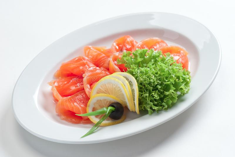 红色鱼内圆角在一块板材的有绿色和柠檬的 免版税库存照片