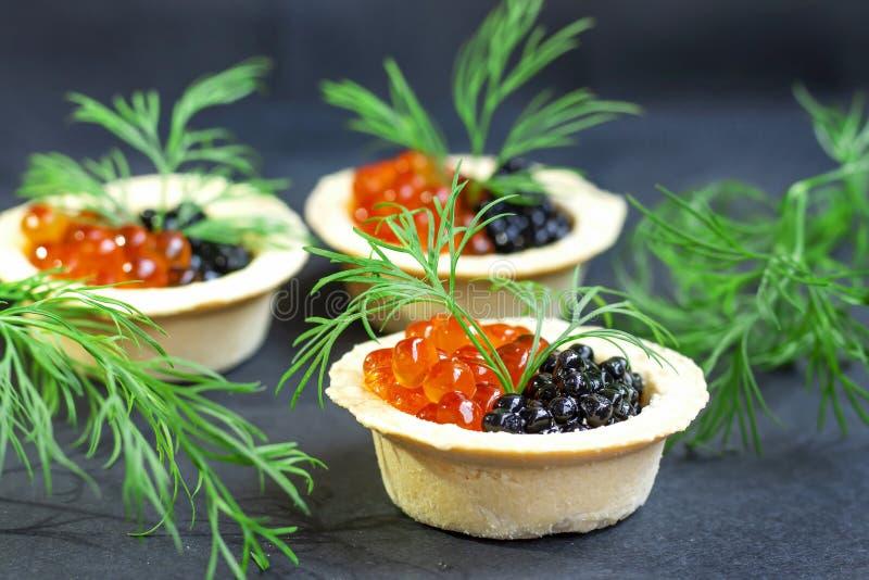红色鱼子酱和黑鱼子酱在果子馅饼 免版税图库摄影