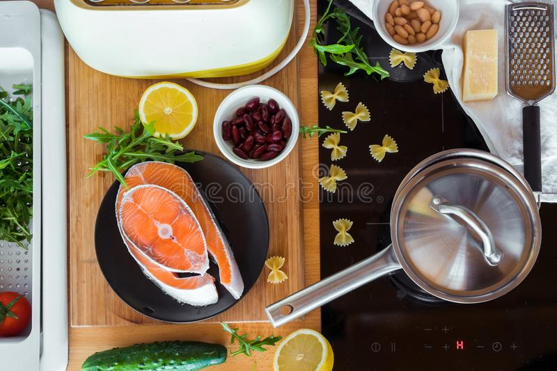 红色鱼片断与菜和其他成份的在木厨房用桌上 库存图片