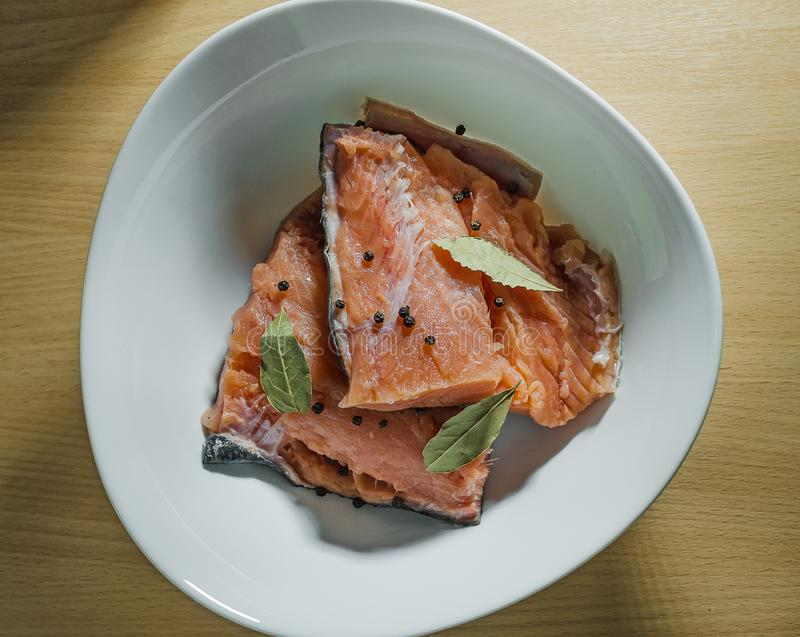 红色鱼用在白色板材的香料 库存照片