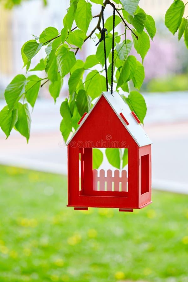 红色鸟房子垂悬从树和包围由茂盛植物 免版税库存照片