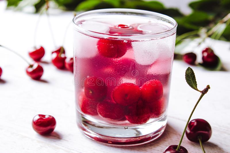 红色鸡尾酒用樱桃和冰在白色木背景 新鲜的夏天鸡尾酒用樱桃和冰块 图库摄影